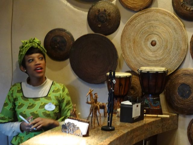 """At the check in desk for Sanaa, Lebo explains that the many baskets on the wall are the sort that are used to clean grain of insects etc. The grain is placed on these baskets and tossed lightly so that the lighter weight """"dirt"""" flies away from the grain. Hidden Mickey alert!"""