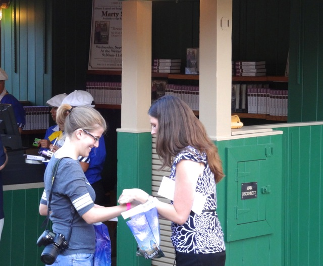 A lady that we don't know is getting her wristband. This proves that she purchased the book from Walt Disney World on the day of the signing - so she can get in line to go into Writer's Stop.