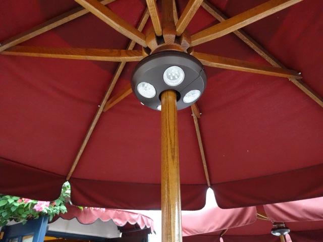"""The tables are nicely """"attired"""", large umbrellas and lights for evening - would have been nice to have a tablecloth, but there's an umbrella coming through the middle"""